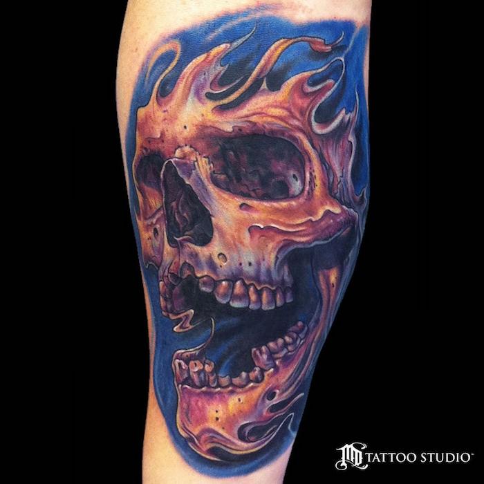 ein tattooo mit einem großen orangen brennenden totenkopf und feuer - bein mit tattoo