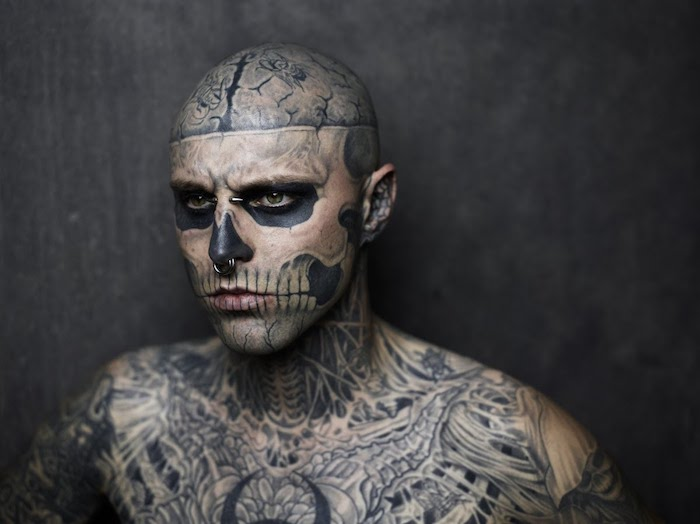 ein tätowierter unger mann mit vielen tattoos und mit einer tätowierung mit einem großen weißen totenkopf mit weißen zähnen und zwei schwarzen augen