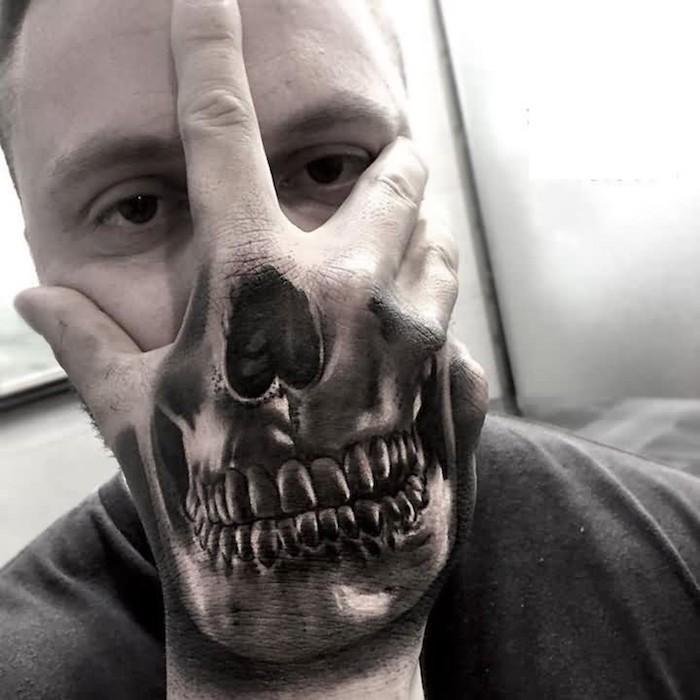 totenkopf tattoo bedeutung - ein junger mann mit einer hand mit einem schwarzen großen tattoo mit einem totenkopf mit zähnen