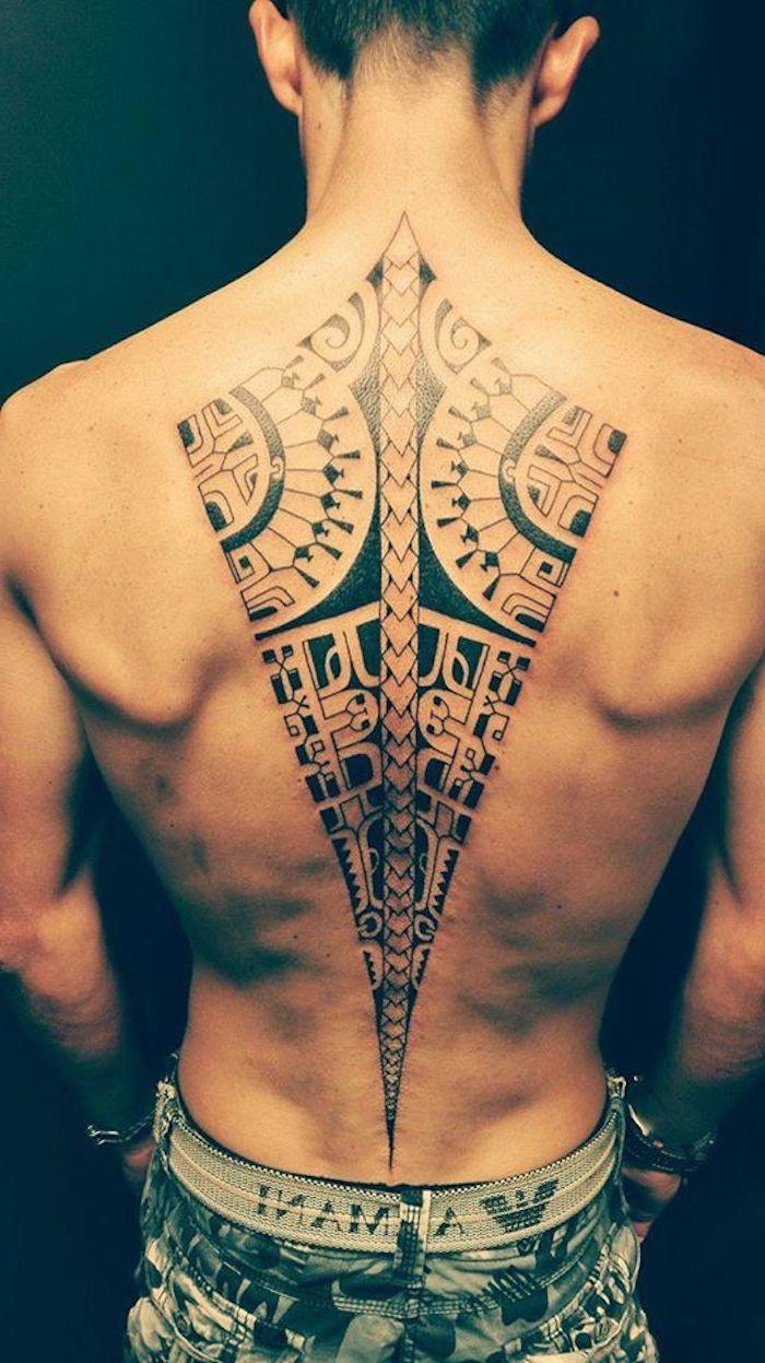 ein großer schwafrzer maori tattoo mit maori tattoo motiven - ein junger mann mit einer schwarzen tätowierung auf dem rücken