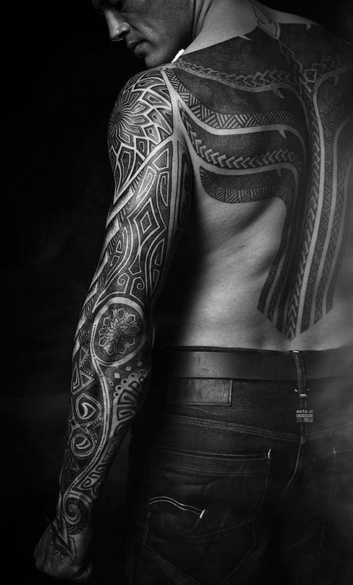 ein junger mann mit einer großen schwarzen maori tätowierung und mit schwarzen hosen - maorie tattoo bedeutung