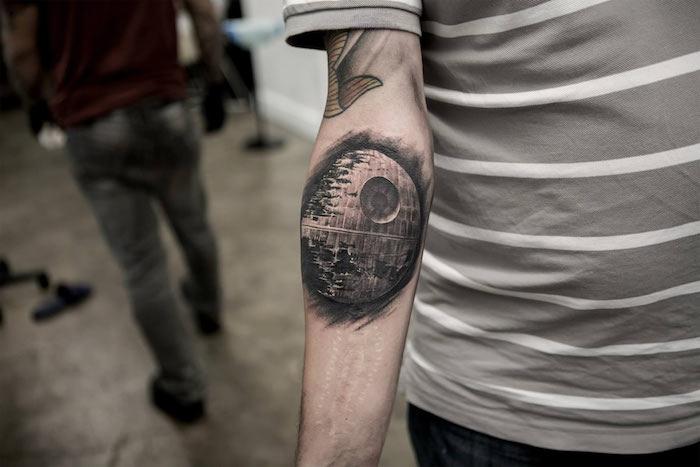 ein mann mit einem tattoo star wars mit einem großen schwarzen raumschiff - eine hand mit tattoo - ein mann mit einem grauen t-shirt