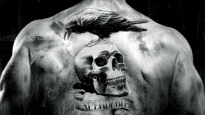 mann mit einem tattoo mit einem schwarzen großen vogel und mit einem großen weißen totenkopf - totenkopf tattoo bedeutung