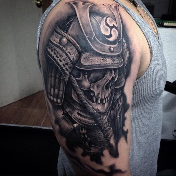 junger mann mit einer hand mit einer großen schwarzen tätowierung mit einer japanische rüstung und einem totenkopf - tattoo totenkopf
