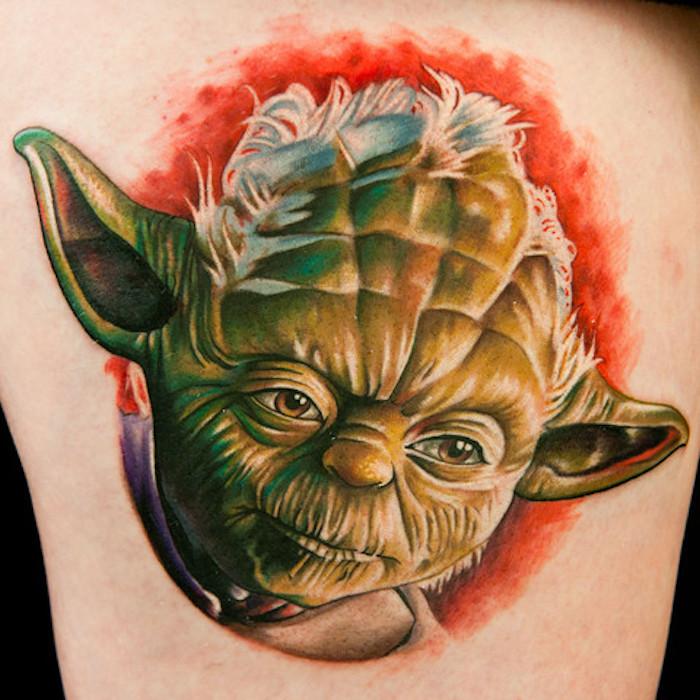 ein großer star wars tattoo mit einem grünen star wars wesen - jedi joda mit großen ohren und grünen augen