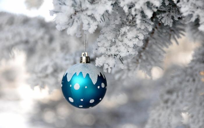 eine kleine blaue weihnachtskugel und ein baum mit schnee - ein romantisches winterbild