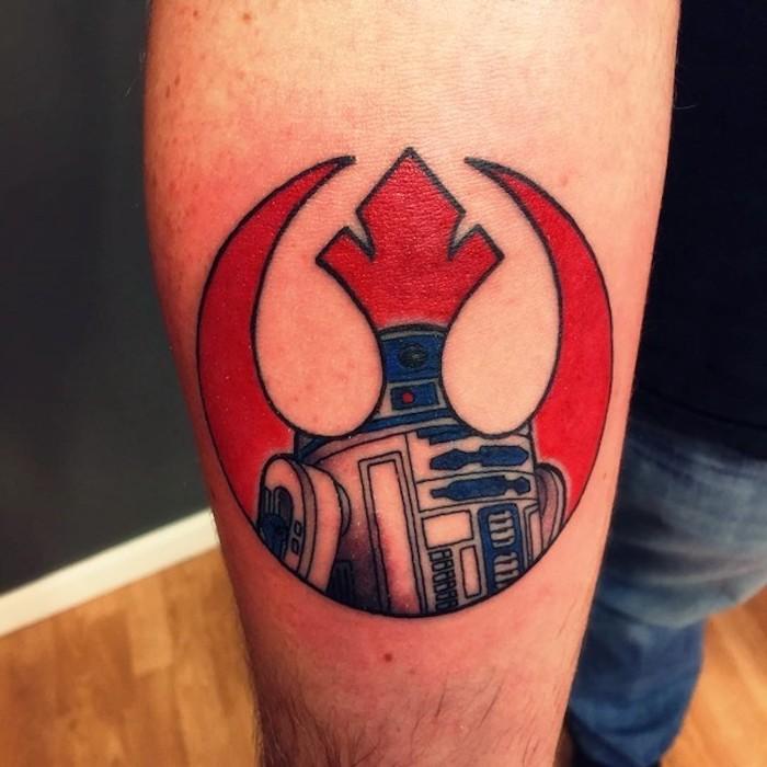 mensch mit hand mit einem großen roten star wars tattoo mit einem star wars logo mit einem roten raumschiff und einem kleinen weißen roboter