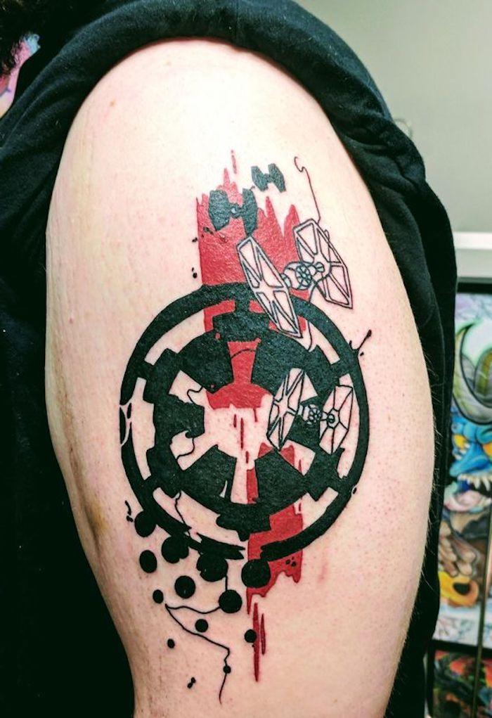 mann mit einer hand mit einem großen star wars tattoo mit einem schwarzen star wars logo und zwei kleinen weißen raumschiffen