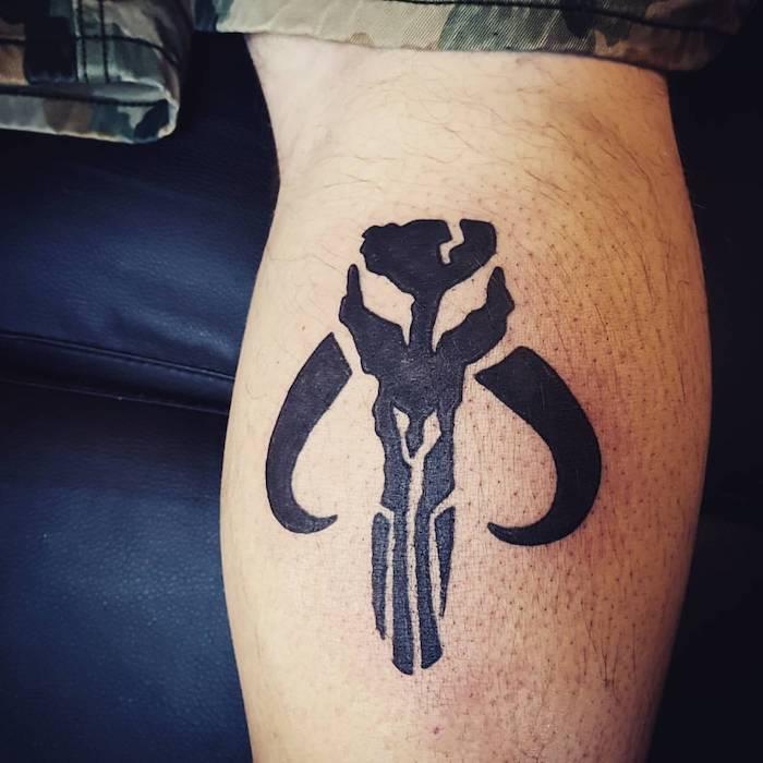 ein mann mit einer hand mit einem kleinen schwarzen star wars tattoo mit einem schwarzen star wars wesen