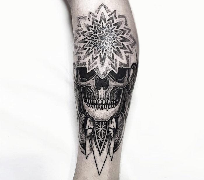 eine hand mit einem traumfänger tattoo mit einem weißen totenkopf mit schwarzen augen und weißen zähnen udn federn