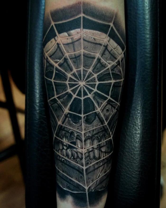 hand mit einem großen schwarzen tattoo totenkopf mit einem großen weißen spinnennetz