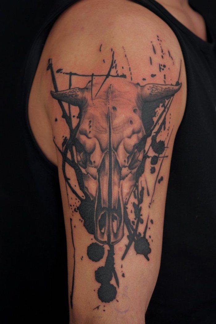 eine hand mit einem tattoo mit einem weißen totenkopf eines tieres mit schwarzen hörnern