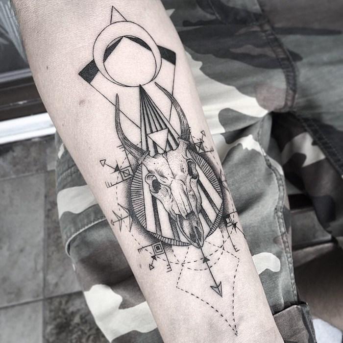 totenkopf tattoo bedeutung - eine hand mit einem tattoo mit einem weißen totenkopf eines tieres mit schwarzen hörnern