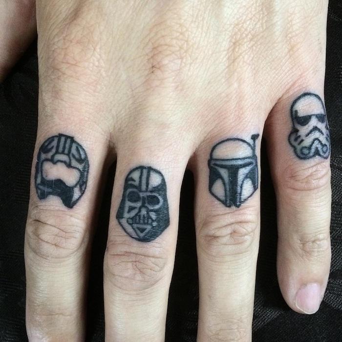 eine hand mit fingern und vier winzigen schwarzen star wars tattoos mit einem schwarzen darth vader und weißen klonen