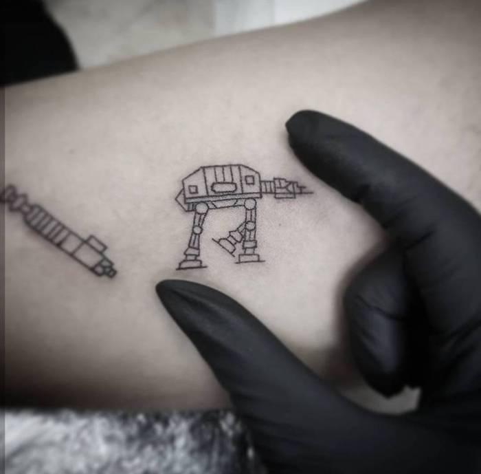 eine hand und ein kleiner schwarzer star wars tattoo mit einem kleinen weißen roboter und einem kleinen weißen lichtschwert