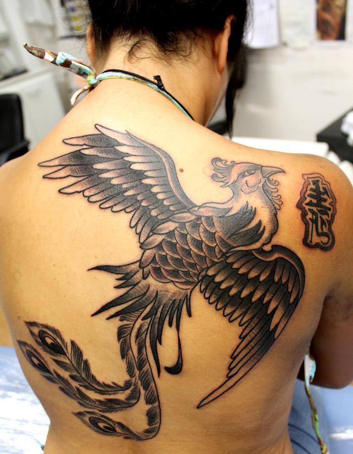 junge frau mit einer schwarzen tätowierung mit einem großen schwarzen fliegenden phönix mit zwei schwarzen flügeln mit schwarzen und weißen federn, phönix Tattoo Rücken Frau