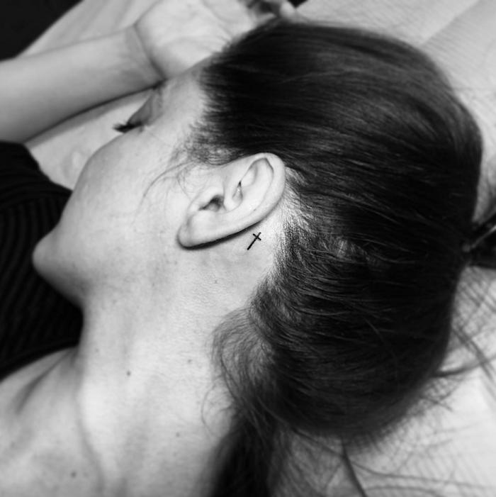 tattoo hinterm ohr motive - eine junge frau mit einem kleinen schwarzen tattoo mit einem schwarzen kleinen kreuz hinter ihrem ohr
