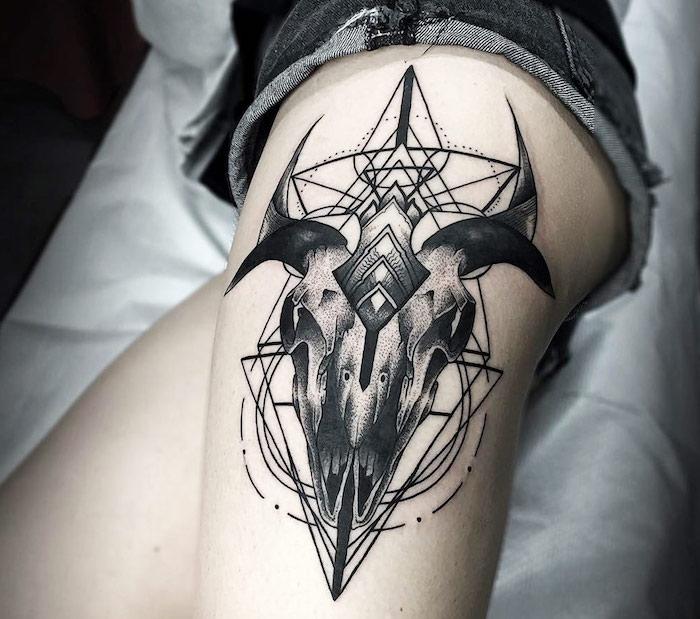 bein mit einem großen tattoo mit einem weißen totenkopf mit schwarzen hörnern