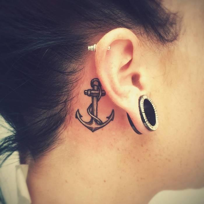 hinterm ohr tattoo - junge frau mit einem großen schwarzen ohrring und einem kleinen schwarzen tattoo hinterm ohr mit einem schwarzen anker