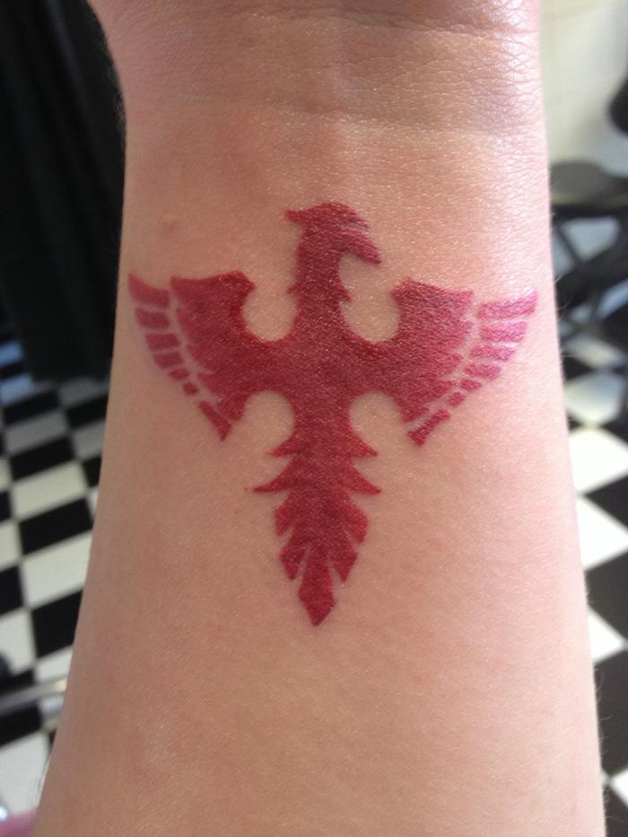 roter tattoo mit einem kleinen roten phönix mit roten flügeln - phönix tattoo am handgelenk