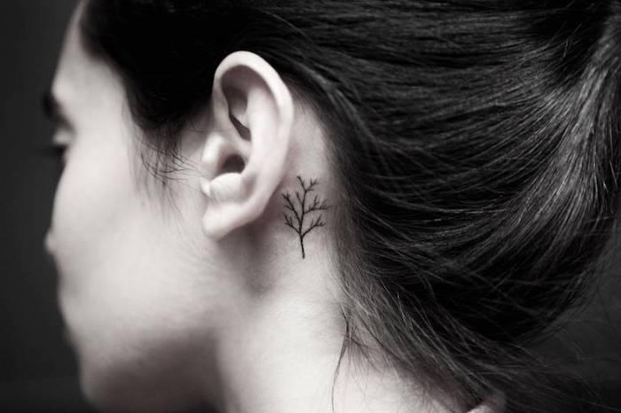 tattoo hinterm ohr motive - eine junge frau mit einem kleinen schwarzen tattoo hinter ihrem ohr mit einem kleinen schwarzen baum