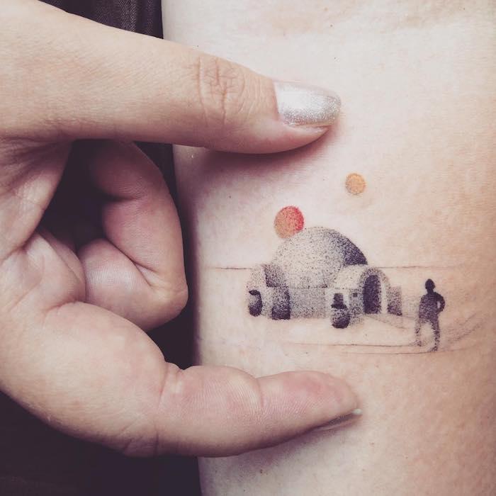 eine hand mit einem star wars tattoo - ein kleiner schwarzer mensch, eine wüste und zwei gelbe sonnen
