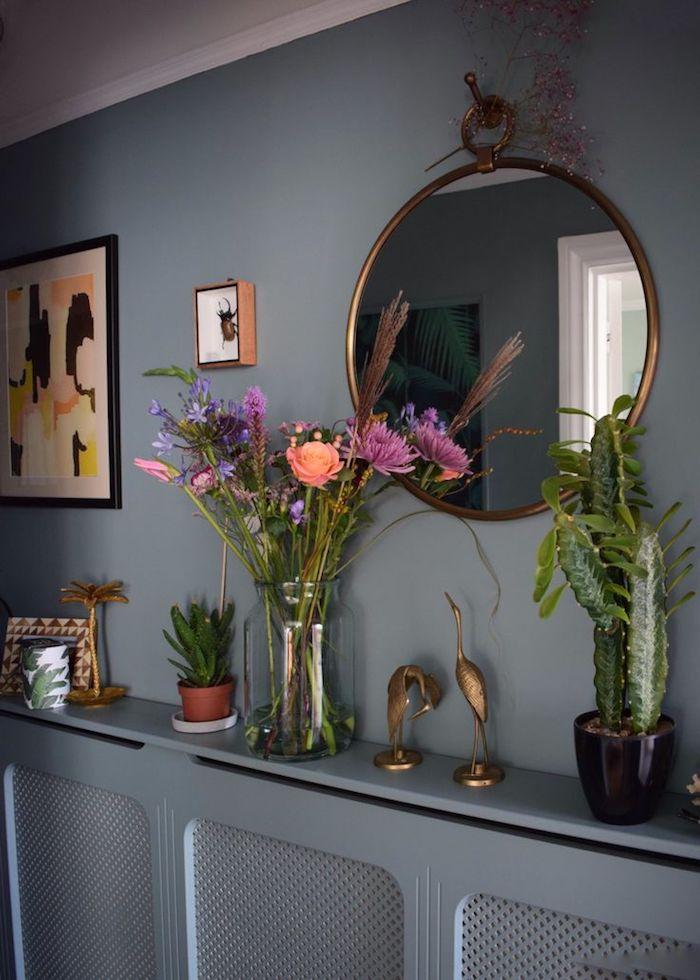 Flur Ideen in Grau-Blau, die beste Idee für Heizungsverkleidung, Wandregal mit vielen Dekoartikeln - zwei Kranich-Figuren aus Edelstahl mit Kupferüberzug, Glasvase mit frischen lila und orangen Blumen, Sukkulentpflanze in einem braunen Topf, großer Kaktus in einem schwarzen Topf, Foto im braunem Rahmen, runder Spiegel im Vintage-Style mit einem Hacken zum Aufhängen, Spiegeldeko aus getrockneten Blumen, abstraktes Wandbild mit fünf Farben, präparierter Hirschkäfer unter einem umrahmten Glas
