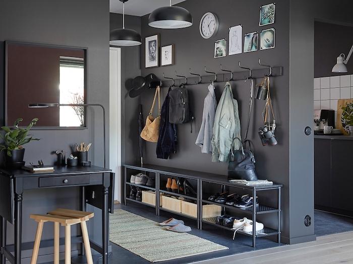 Wohnung mit dunkelgrauen Wänden, Eingang mit dunklen Möbeln, Schuhregal mit vielen Schuhen für Männer und Frauen, orange Veloursschuhe mit Absatz, hellblaue Plüsch-Pantoffel, schwarzer Spiegeltisch mit einer Schublade, Holzhocker in Hellbraun, quadratischer Spiegel mit schmalem Rahmen, einklappbarer Holztisch mit einer Lampe, grüne Pflanze in schwarzem Topf, Küchenrückwand mit weißen Fliesen, Wand mit einer runden Uhr und vielen Bildern, Hänger mit vielen Jacken und vielen Taschen, Industrial-Kronleuchter mit schwarzen Schirmen