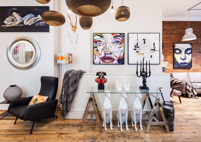 kitschige Flur Ideen, Wohnung mit abstrakten und surrealistischen Bildern, Porträt in grellen Farben, runder Designer-Spiegel mit silbernem Rahmen, Designer-Stehlampe mit buntem Kronleuchter in Pastellfarben, schwarzer Lederstuhl mit Armlehnen, orange Kissen mit grünem Motiv, graue dekorative Vase mit runder Form, graue Kuscheldecke mit Print, Designer-Kronleuchter mit Papierschirmen, Glastisch mit Metallbeinen, drei dekorative weiße Hunde, schwarzer Gothik-Kerzenleuchter für fünf Kerzen, Holzboden aus künstlich veraltetem Holz, Flur mit weißen Wänden, Flur mit Übergang zum Wohnzimmer, Wohnzimmer mit Ziegelwand, schwarz-weißes Mädchen-Porträt, graue Couch mit Armlehnen, Polsterstuhl mit Holzbeinen, Zimmer mit weißer Decke