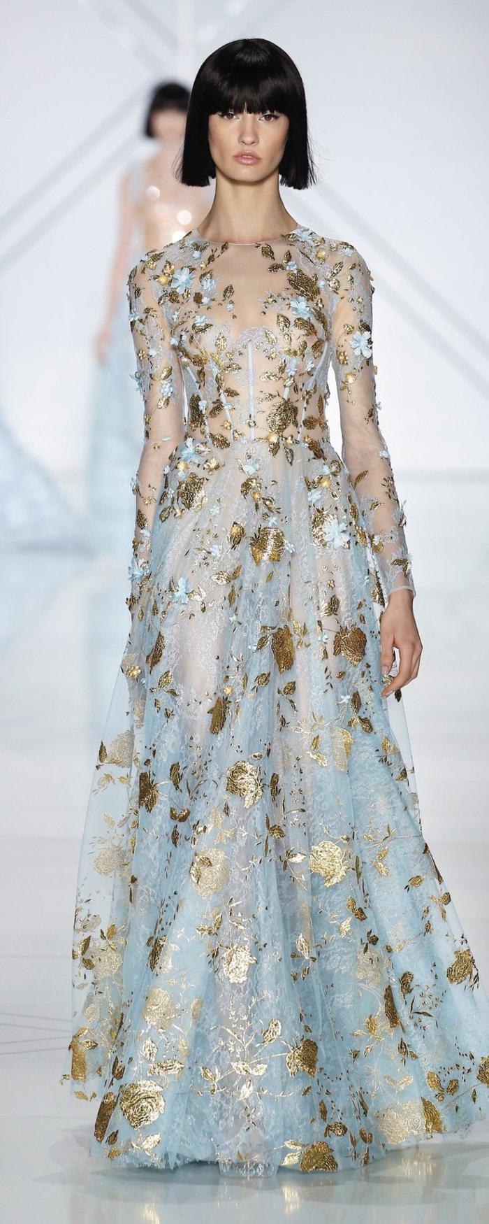 strickter Haarschnitt für kurze Haare mit geradem Pony, sehr langes feerisches Kleid in Hellblau mit goldenen Applizierungen