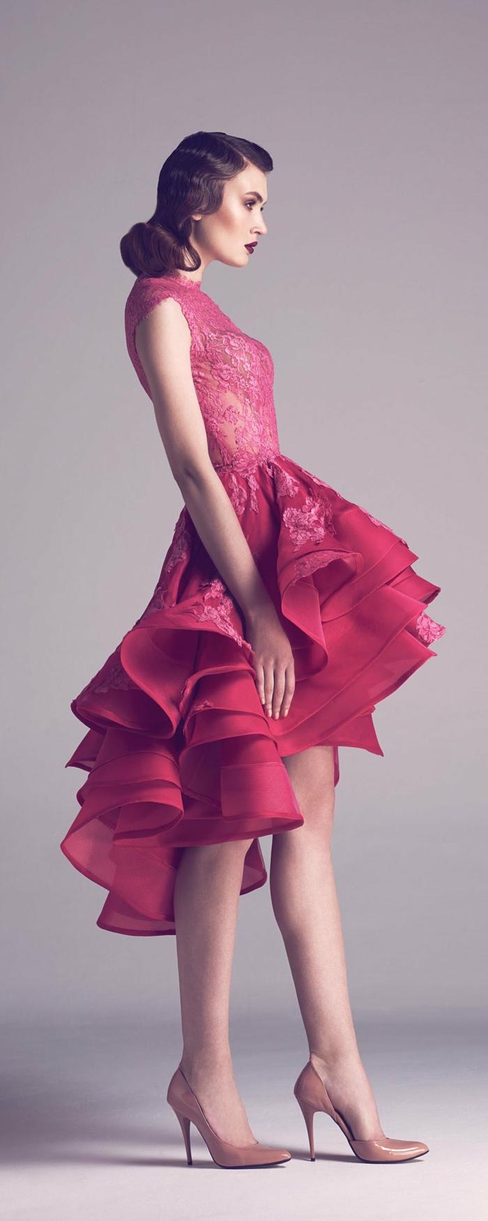 Frisur mit Volumenwelle und Seitenscheitel, pinkes Kled mit Oberteil aus Spitze und Plissee-Unterteil, pinkes Kleid, das vorne kürzer und hinten länger ist, Spitze mit Blumenmotiven, Lackschuhe mit Absatz in Beige