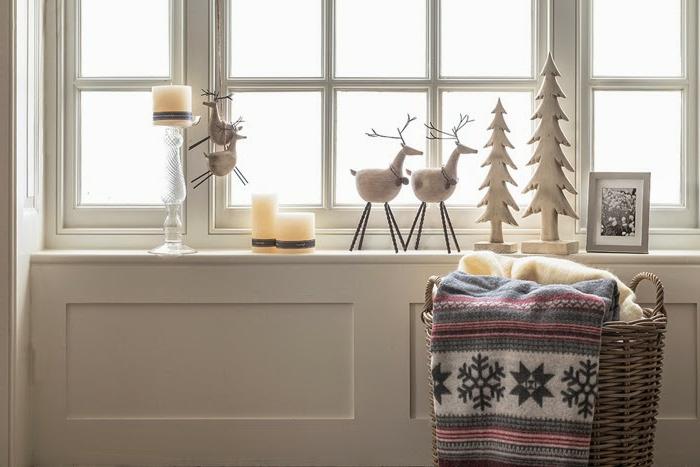 Fensterbank weihnachtlich dekorieren - zwei Tannenbäume aus Holz, gestrichen in Weiß, schwarz-weißes Foto mit grauem Rahmen, drei große Kerzen, dekoriert mit Bindfäden, Kerzenhalter aus Glas, zwei Hirsch-Figuren zum Aufhöngen, zwei Hirschfiguren aus Baumwolle und Holz, großer Flechtkorb mit zwei Schlafdecken - eine gelbe Kuscheldecke und eine Decke mit Schneeflocken-Mitove, weiße Wand mit Holzverkleidung