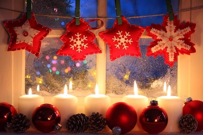 fensterdeko zu weihnachten kerze vier adventskerze und vier deko stücken am fenster sterne und tannenbäume aus stoff