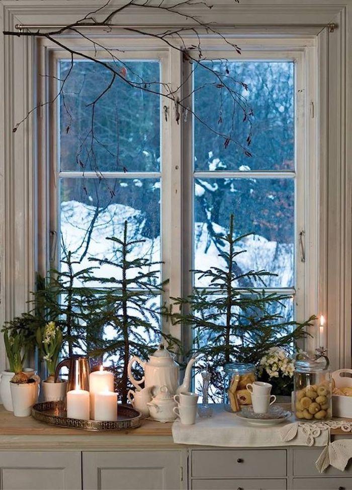 fensterdeko zu weihnachten hölzernes fenster in weißer farbe dekoriert von kerzen grünen zweigen u.a.