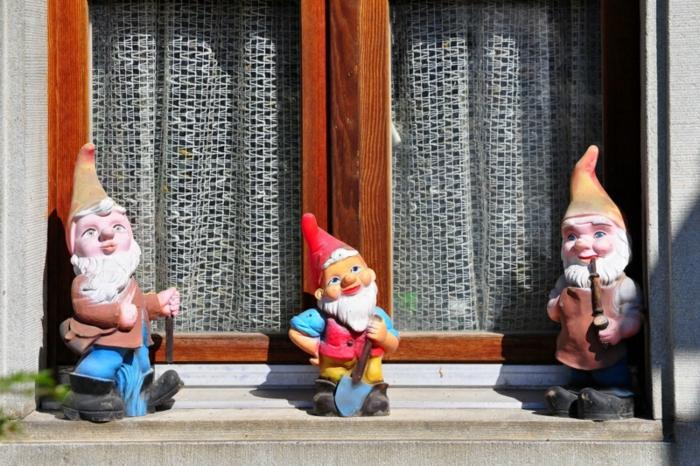 altes Haus mit altmodischen weißen Gardinen mit kleinen Löchern, altmodische Weihnachtsdeko aus Keramikfiguren, drei Keramik-Zwerge auf dem äußeren Fenstersims, drei Gartenzwerge aus Keramik