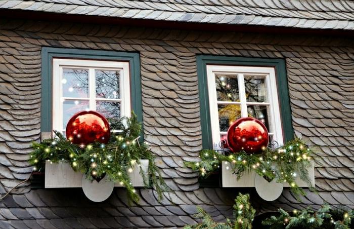 Holzhaus mit Schrägdach und zwei kleinen Fenstern mit Doppellrahmen, äußere Fenstersimse dekoriert mit Nadelbaumzweigen mit Lichterketten und zwei riesengroßen roten Weihnachtsbaumkugeln mit Glanz