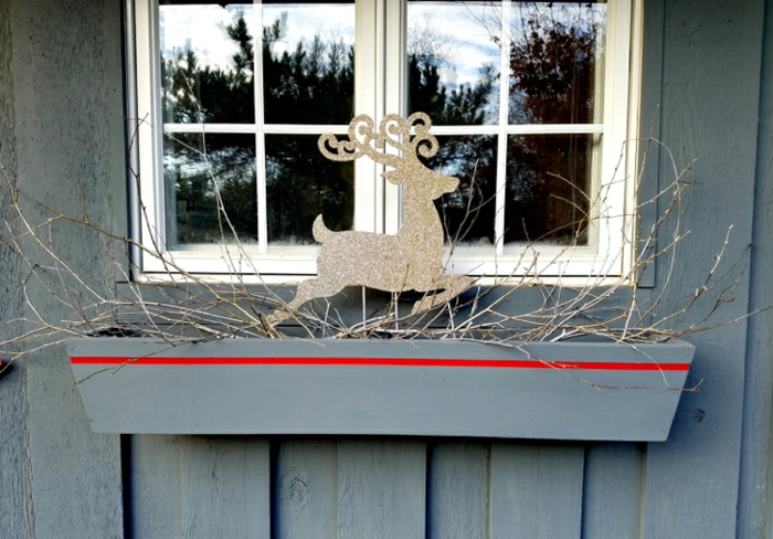 schönes Dekoelement aus Karton - scöner Hirsch mit großem Geweih, besprüht mit Goldspray mit Glitzer, trockene Baumzweige in einem grauem Blumenkasten aus Holz, der eine dünne rote Linie hat, kleines Fenster mt Aussicht zum Hinterhof, Haus mit grau gestrichenen Holzwänden