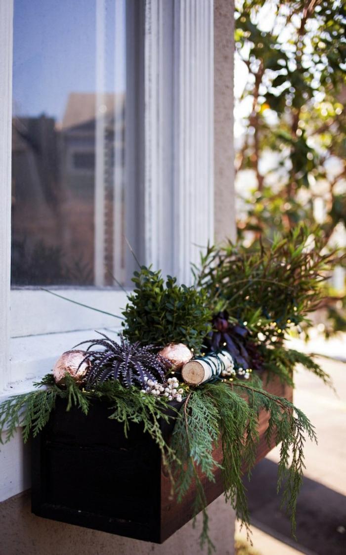 Blumenkasten auf der äußeren Seite der Fenster mit verschiedenen Arten von Pflanzen - Kieferbaumzweige, Sukkulentpflanen und andere, einige Christbaumkugeln in Champagne-Farbe, großes Baum auf der rechten Seite des Hauses