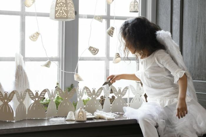 Deko aus Papier - DIY Engel aus Papier, Papierlaterne mit vielen Löchern, Papiergirlande für das Fenster, frische grüne Kieferzweige, ein kleines Mädchen, gekleidet komplett in Weiß, kleines Mädchen mit dunklen mittellangen Haaren und weißen Kleidern -lange weiße Hose und weiße Bluse mit Ärmeln bis zum Ellenbogen, Mädchen mit weißen Engelflügeln aus echten Federn, grau gestrichene Fensterbank, grau gestrichene Holzwan