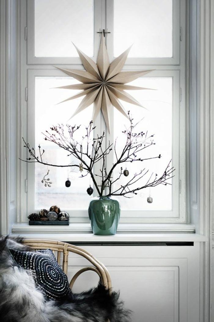 großer Origami-Stern aus Bastelpapier, trockene Baumzweige in einer grünen Vase mit Glanzüberzug, Baumzweige mit Weihnachtsdeko, kleine viereckige Kiste in dunkler Farbe mit Zapfen und Christbaumkugeln, Holzstuhl mit einer grauen Plüschdecke und einem schwarzen Kissen mit weißem Spiralen-Motiv
