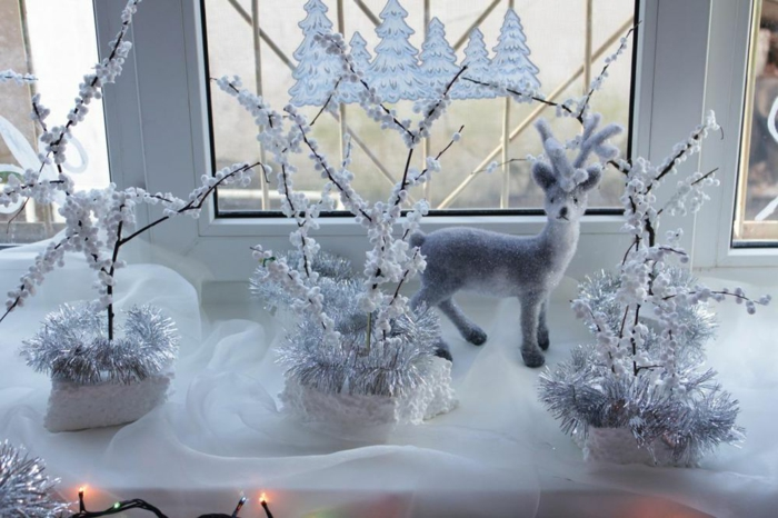 elegante Weihnachtsdeko in Weiß - drei Baumzweige, verziert mit Knallmais und silbernen Girlanden, gesteckt in drei weién Styropor-Stücken, kleine weiße Hirsch-Figur, gestellt vor dem Fenster aus einer halbtransparenten weißen Tülldecke, Weihnachtsbaum-Kleber am Fenster, Lichterkette mit kleinen gelben Lampen