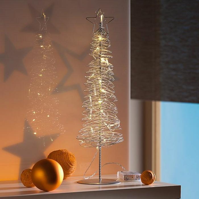 Tannenbaum aus Metalldrahtmit kleinen Lampen und einen Weihnachtsbaumstern an der Spitze, ein großer Kugel mit Goldüberzug, drei gelbe Weihnachtsbaumkugeln, Fensterrollo in grauer Farbe