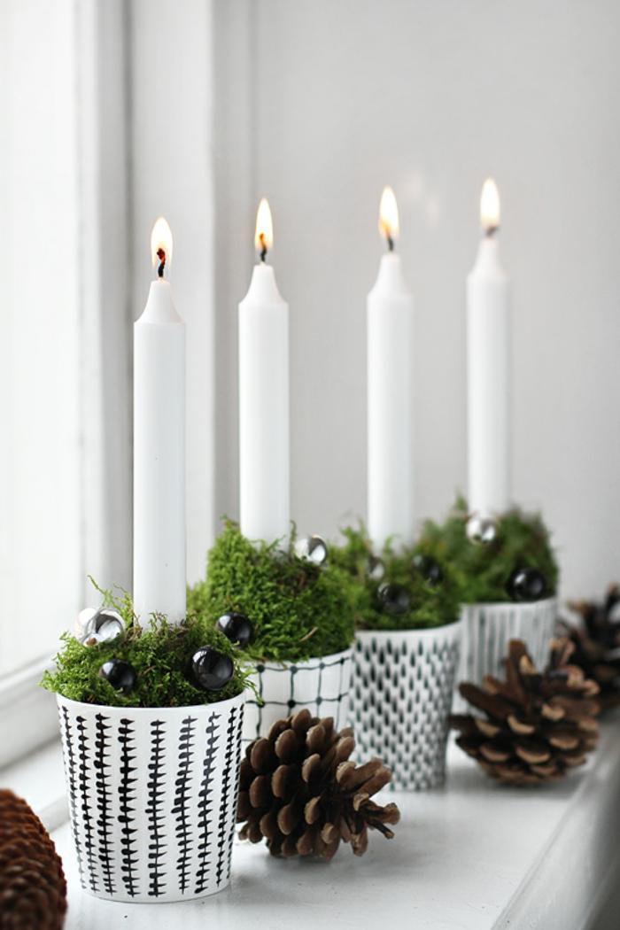 vier gezündete Kerzen aus weißem Wachs in vier schwarz-weißen Papierbechern, gefüllt mit frischem grünem Grass und kleinen schwarzen Kugeln