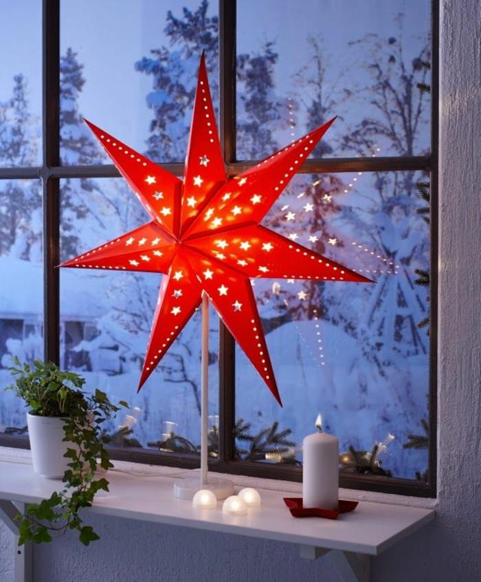 Stehlampe mit rotem Papier-Schirm in der Form eines Sterns, angezündete Kerze aus weißem Wachs, grünes Rankengewächs in einem weißen Blumentopf aus Keramik, Winterlandschaft mit viel Schnee