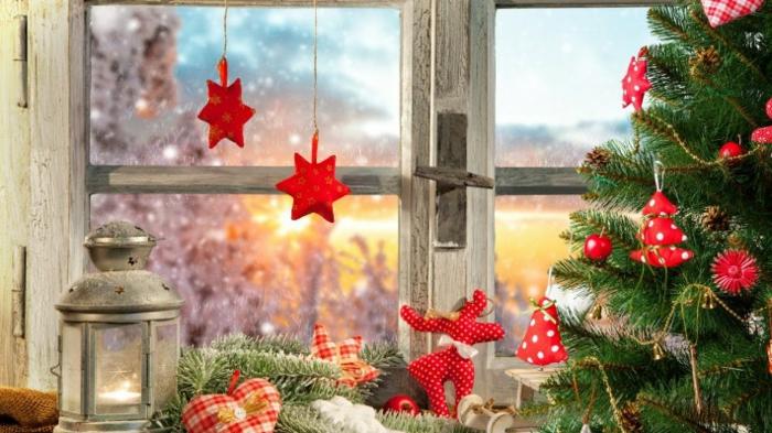 aufgestellter Tannenbaum mit roten Weihnachtsdekorationen aus Stoff, Weihnachtsbäume aus rotem Stoff mit weißen Punkten, Tannenbaum mit Lichterkette, Dekoelement in der Form eines Herzens, Deko-Herz aus kariertem Stoff, Latenr mit Metalldeckel, rote Weihnachtssterne am Fenster