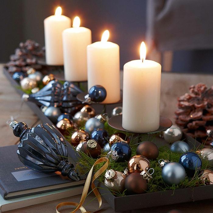 vier Kerzen auf schwarzen Kerzenhaltern aus Edelstahl, kleine Tannenbaumkugeln in verschiedenen Farben mit Glanz- und Mattüberzug, Dekoelement für den Weinachtsbaum aus blauem, leicht zerbrechlichem Glas, zwei große Zapfen auf einem reichlich dekorierten Tisch, zwei Bücher - eins mit dunkelblauem und eins mit hellgrünem Umschlag