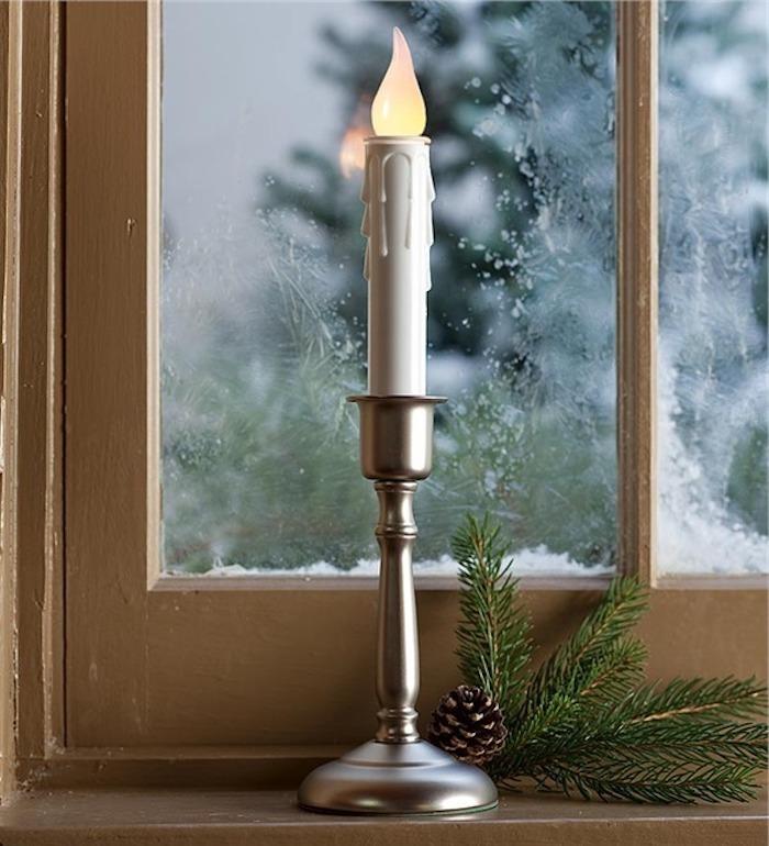 fensterdeko eine einzelne kerze auf schönem ständer mit zweig deko design und zapfen