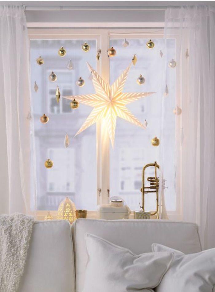 weihnachtliche deko dekorative elemente an dem fenster im wohnzimmer in weißer farbe stern leuchtend festliche laune gestalten
