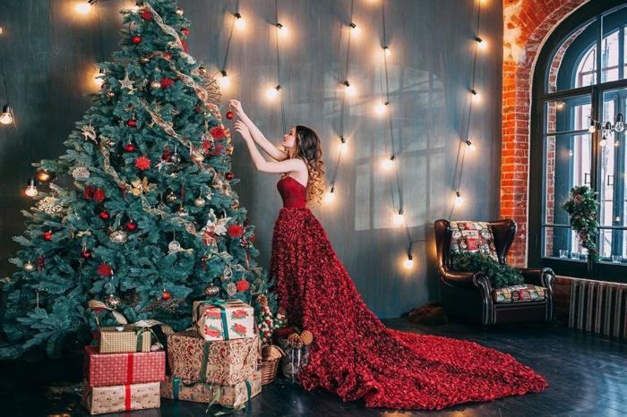 Rotes Abendkleid mit Schleppe, Frau schmückt Weihnachtsbaum, Lichterketten an der Wand, viele Geschenke unter dem Christbaum