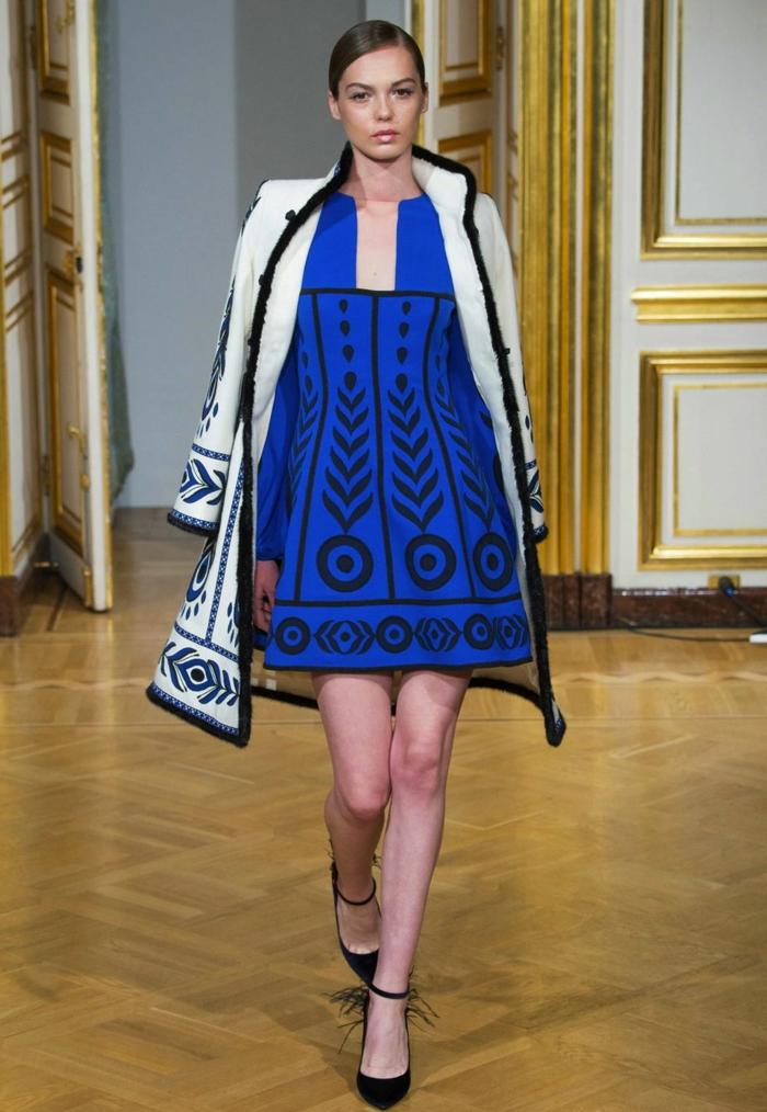 kurzes Kleid in Kaiserblau mit schwarzem Print mit Kreisen und Pfeilen, kombiniert mit einem weißen Wintermantel aus Plüsch mit demselben Print, mit schwarzem Kragen und schwarzen Knöpfen